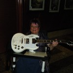 Trish holding guitar autographed by Zoot members